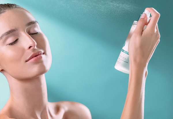 Woman applying Repechage skincare by spraying on her face